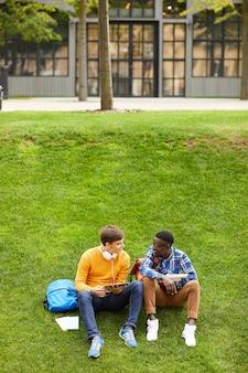 芝生で休んでいる2人の学生