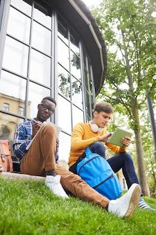 芝生に座っている2人の学生
