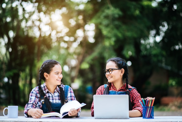 Two students studying together online with a laptop in the park