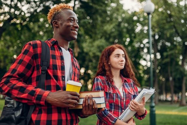 두 학생이 여름 공원에서 보도를 걷습니다. 남성과 여성의 백인 청소년 야외