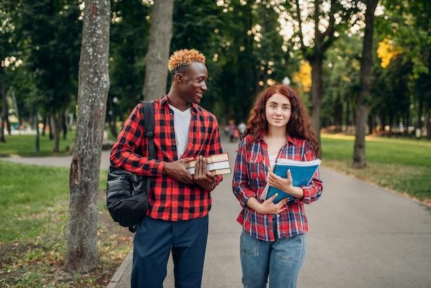 두 학생이 여름 공원에서 보도를 걷습니다. 남성과 여성의 백인 청소년 야외에서 휴식