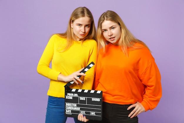 화려한 옷을 입고 두 멋진 젊은 금발 쌍둥이 자매 소녀는 보라색 파란색 벽에 고립 된 clapperboard를 만드는 고전적인 검은 영화를 개최합니다. 사람들이 가족 라이프 스타일 개념.