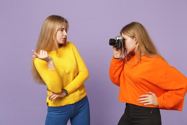 Две потрясающие молодые блондинки-сестры-близнецы в яркой одежде фотографируют на ретро-винтажную фотокамеру, изолированную на фиолетово-синей стене. концепция семейного образа жизни людей.