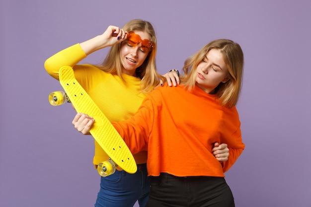 鮮やかな服を着た2人の見事な若い金髪の双子の姉妹の女の子、ハートの眼鏡はパステルバイオレットブルーの壁に分離された黄色のスケートボードを保持します。人々の家族のライフスタイルの概念。 。