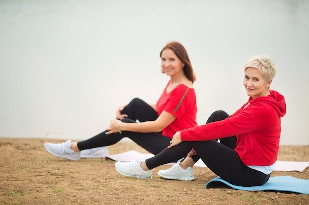 2人のスタイリッシュな大人の女性が湖の近くで夏にアウトドアスポーツをします