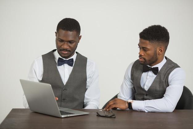 정장에 두 세련된 아프리카 남자는 흰 벽에 노트북과 함께 테이블에 앉아있다