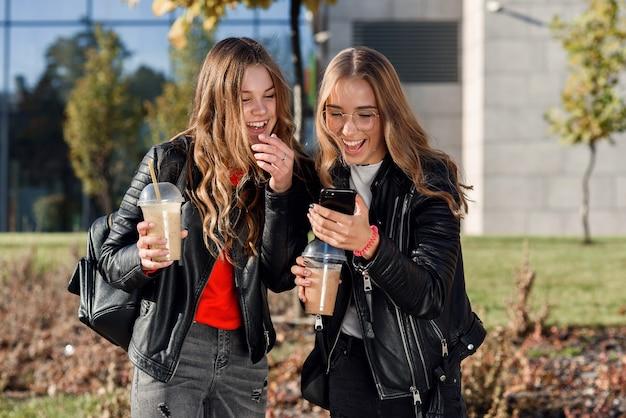 市内中心部のショッピングモールの近くにスムージーとスマートフォンを持つ2人のスタイリッシュで魅力的な10代の少女。