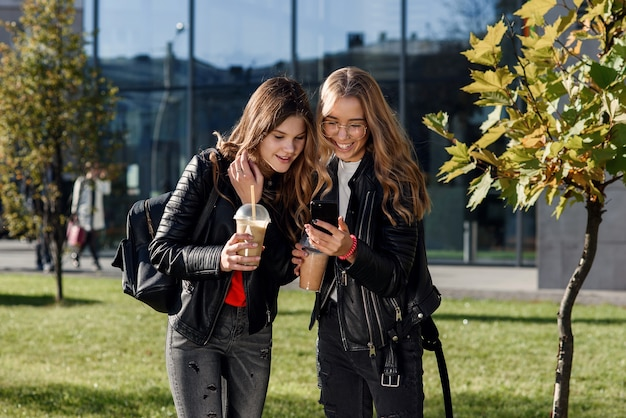 Две стильные привлекательные девочки-подростки с коктейлем и смартфоном возле торгового центра в центре города.