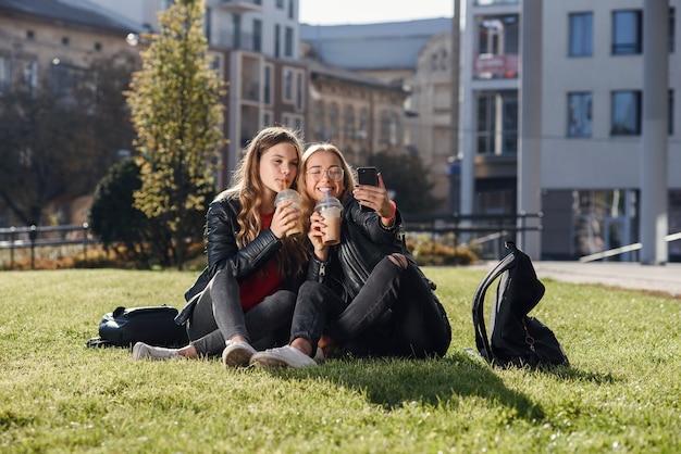 芝生の上に座っているスムージーとスマートフォンを持つ2人のスタイリッシュで魅力的な10代の少女。親友との余暇。