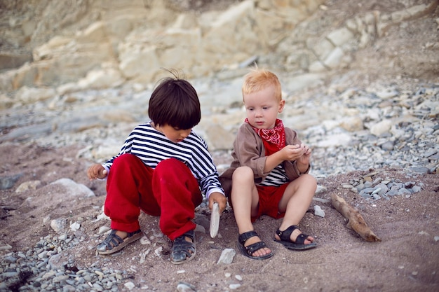 Two stylish baby boys in vests sit on the seashore of pebbles in summer