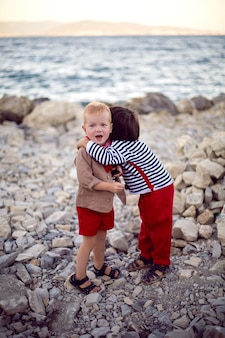 Two stylish baby boys in vests stand on the seashore of pebbles in summer