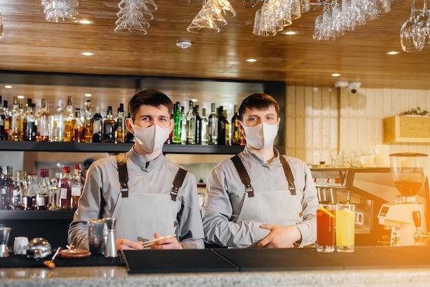 パンデミックの際にマスクとユニフォームを着た2人のスタイリッシュなバーテンダーが、カクテルを準備します。パンデミック時のレストランやカフェの仕事。