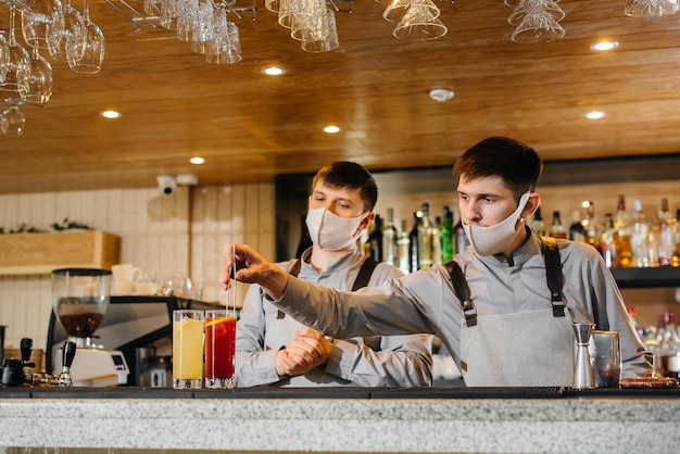유행하는 동안 마스크와 유니폼을 입은 두 명의 세련된 바텐더가 칵테일을 준비합니다. 대유행 기간 동안 레스토랑과 카페의 작업.