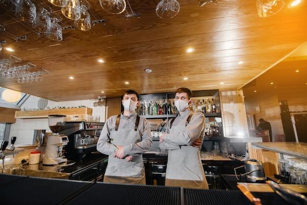 대유행 기간 동안 마스크와 유니폼을 입은 두 명의 세련된 바텐더가 바 뒤에 서 있습니다. 대유행 기간 동안 레스토랑과 카페의 작업.