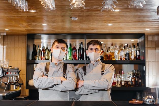 За барной стойкой стоят два стильных бармена в масках и униформе во время пандемии. работа ресторанов и кафе в период пандемии.