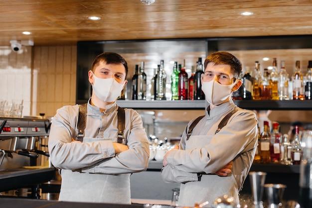 За стойкой стоят два стильных бармена в масках и униформе во время пандемии. работа ресторанов и кафе в период пандемии.