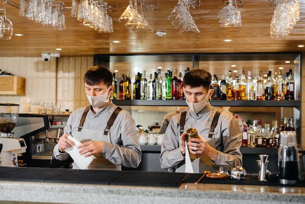 Two stylish bartenders in masks and uniforms during the pandemic, rub glasses to shine. the work of restaurants and cafes during the pandemic.