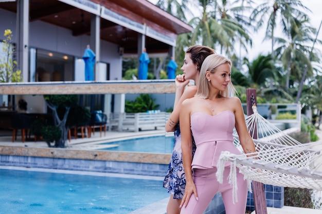 夏のドレスとピンクの流行のスーツの2つのスタイリッシュな白人女性