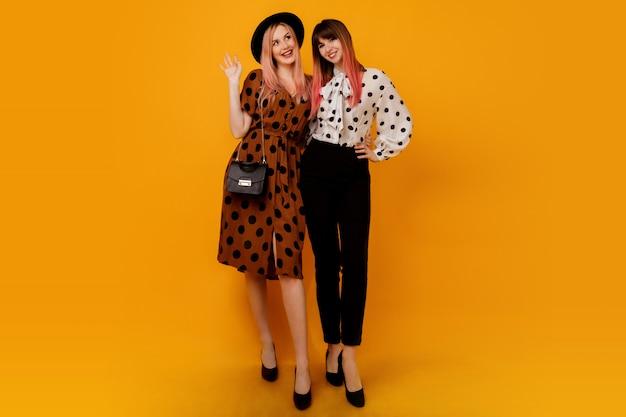 Две стильные элегантные женщины в платьях позируют на желтой стене