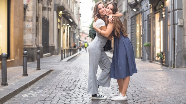 Two stylish female friends standing on street hugging each other