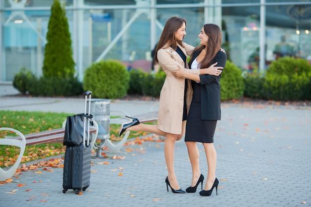 空港で荷物を持って歩く2人のスタイリッシュな女性旅行者