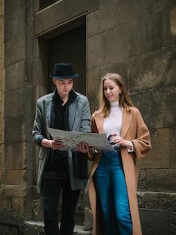 通りに立って地図を使って何かを探すスタイリッシュな2人の友人。彼らは周りを見回しています。彼らは、共同散歩のピークと魅力的です。