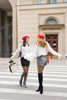 Two stylish girlfriends with red berets in the style of french women smile and laugh, walking around the city, with shopping bags