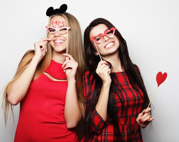 白のパーティーの準備ができている赤いドレスを着た 2 人のスタイリッシュな女の子の親友