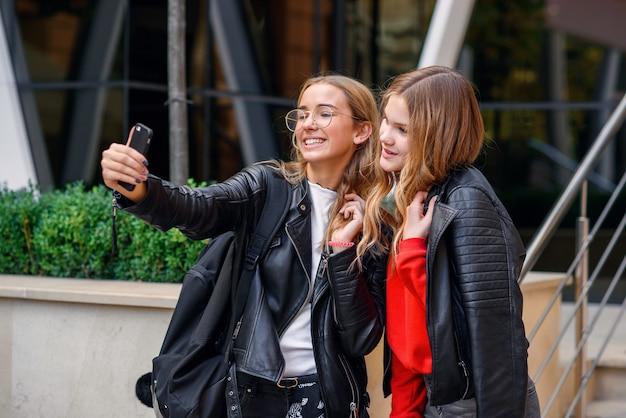 通りのスタイリッシュなモダンな建物の近くで自分撮りを作るスマートフォンを持つ2人のスタイリッシュな幸せな10代の少女。
