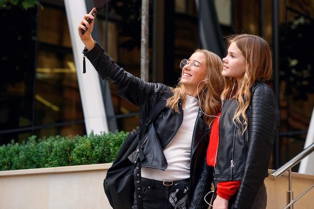 Two stylish happy teenage girls with smartphone making selfie near stylish modern building on the street.