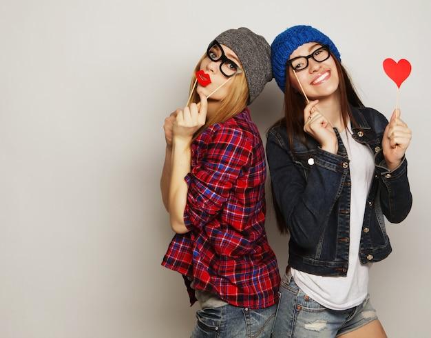 灰色の2人のスタイリッシュな流行に敏感な女の子の親友がパーティーの準備ができています