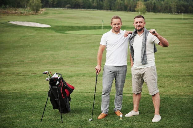 Два стильных мужчины держат сумки с клюшками и гуляют по гольфу