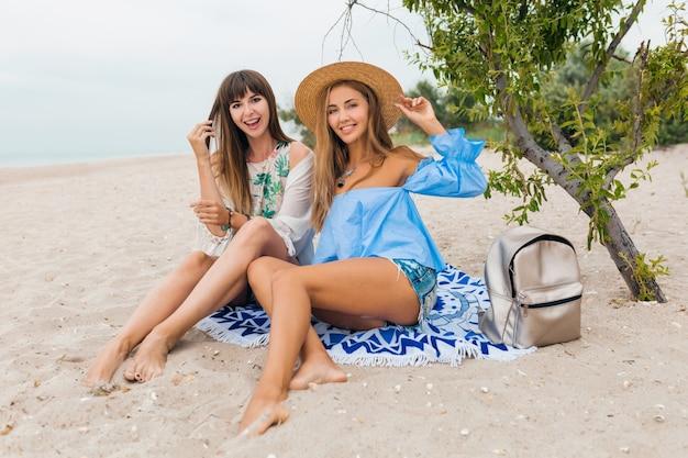熱帯のビーチで夏休みに砂の上に座っている2人のスタイリッシュなかなり笑顔の女性、友達が一緒に旅行します。