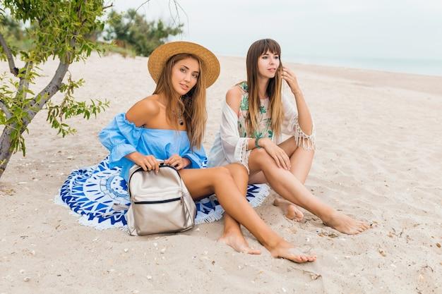 Две стильные симпатичные улыбающиеся женщины, сидящие на песке на летних каникулах на тропическом пляже, друзья путешествуют вместе