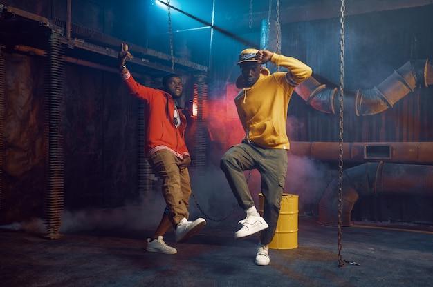 クールな地下装飾が施されたスタジオでブレイクダンスをする2人のスタイリッシュなラッパー