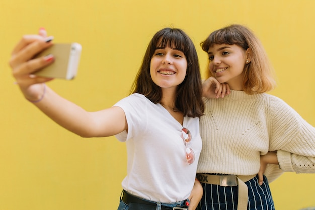 Two stylish school friends girl joking makes selfie and smiling on the yellow background.