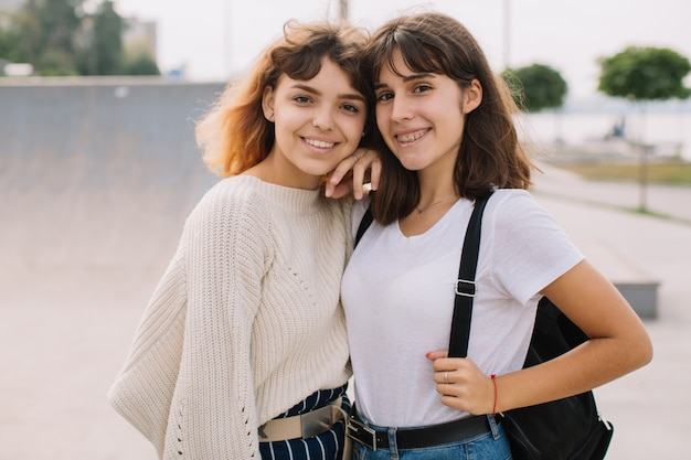 Two stylish school friends girl joking and smiling on the street.