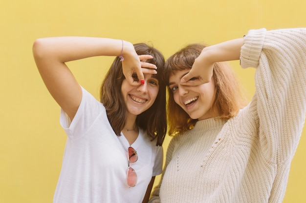 Two stylish school friends girl joking and smiling on the yellow background.