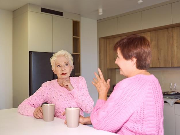 Две стильные пожилые женщины в розовых свитерах сидят с кружками на современной кухне и сплетничают