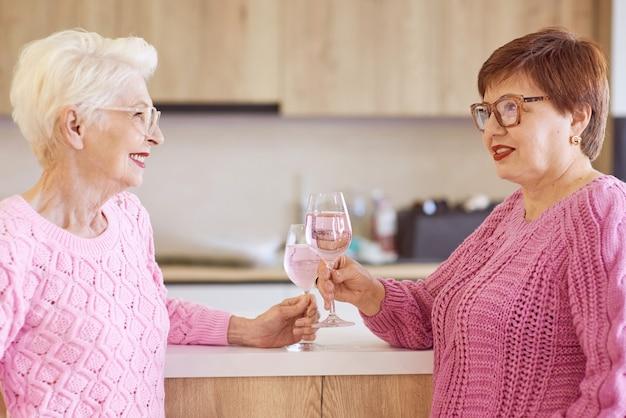 Two stylish senior women in pink sweaters drinking rose wine at modern kitchen gossiping