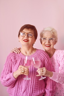 Two stylish senior women in pink sweaters with rose wine glasses on pink background