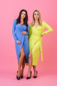 Две стильные сексуальные привлекательные женщины позируют в полный рост на розовой стене в стильных красочных платьях синего и желтого цвета, весенняя мода