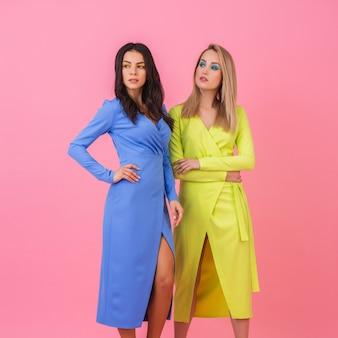Две стильные сексуальные привлекательные женщины позируют в полный рост на розовой стене в стильных красочных платьях синего и желтого цвета, тренд летней моды