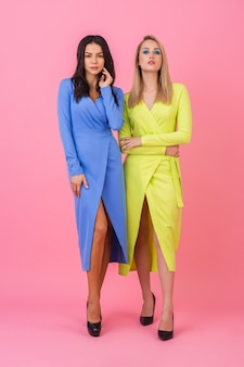 Two stylish sexy attractive women posing full height on pink wall in stylish colorful dresses of blue and yellow color, summer fashion trend