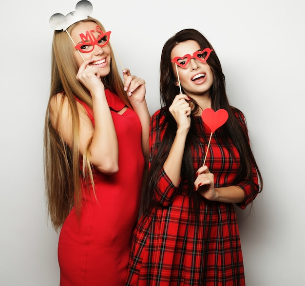Two stylish sexy  girls best friends wearing red dress  ready for party, over white background