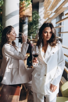 Two stylish sexy glamour elegant women wear white suits in a restaurant with a glass of wine.