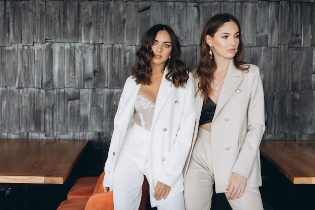 Two stylish sexy glamour elegant women wear white suits in a restaurant.