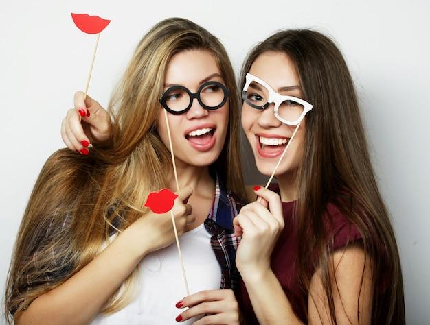 Две стильные сексуальные хипстерские девушки лучшие друзья готовы к вечеринке, на сером фоне