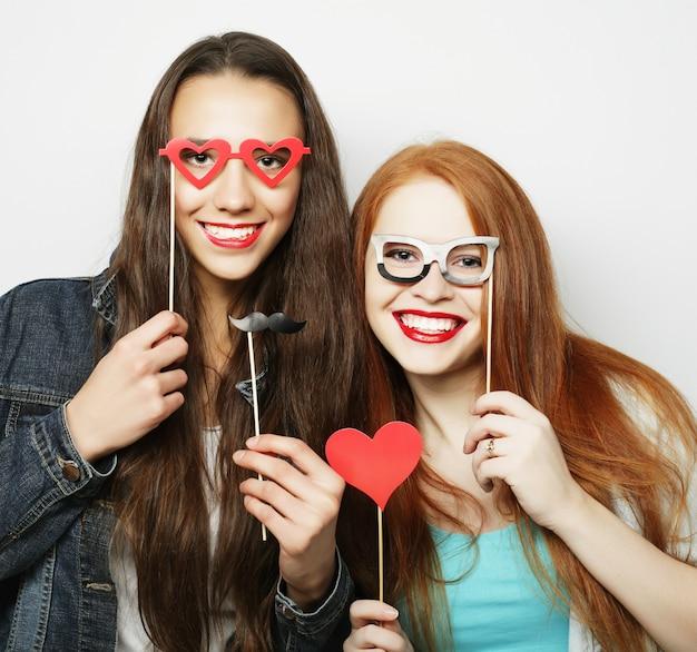パーティーの準備ができている2人のスタイリッシュなセクシーな流行に敏感な女の子の親友