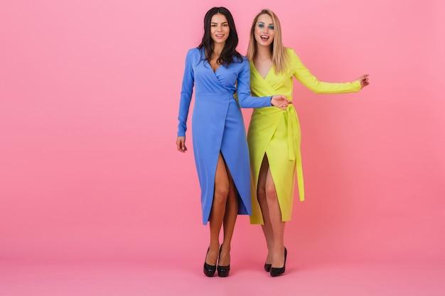 Две стильные сексуальные улыбающиеся привлекательные блондинки и брюнетки позируют на розовой стене в стильных красочных платьях синего и желтого цвета, тренд летней моды